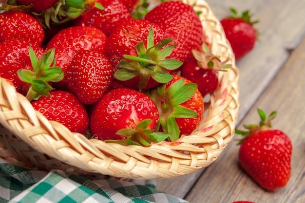 Корзина урожая клубники на деревянном столе крупным планом Premium Фотографии