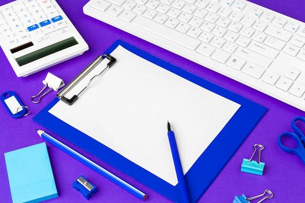紫色の背景にオフィスライフスタイルアイテムの組成、オフィスの机の上のコンピューターキーボードオフィス用品 Premium写真