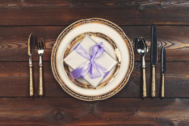 ライラック色の木製のテーブルの休日テーブルの設定 Premium写真