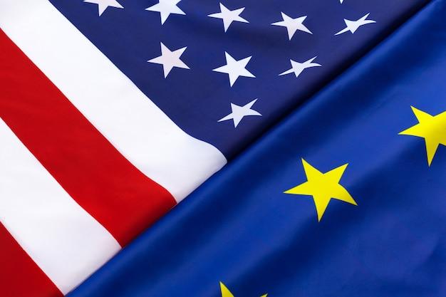 テーブルの上に一緒に横になっている米国および欧州連合の旗のクローズアップ Premium写真