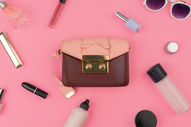 明るいピンクの背景に化粧品の完全な女性の小さなハンドバッグ Premium写真