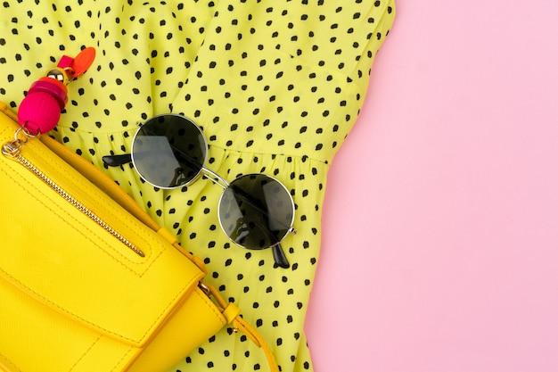 Стильный летний наряд для женщины на пастельном розовом фоне Premium Фотографии