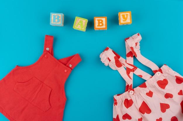 Вид сверху детской одежды на синем фоне Premium Фотографии