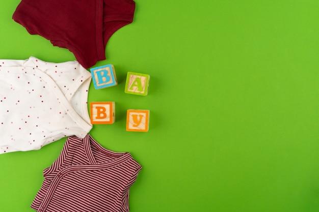 Вид сверху детской одежды на зеленом фоне Premium Фотографии