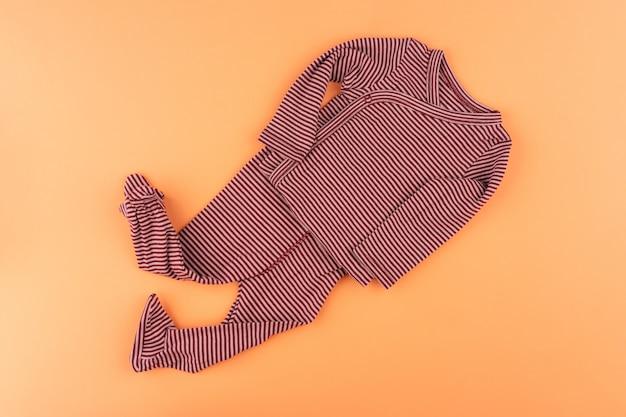 オレンジ色の背景の上面に女の赤ちゃんの服 Premium写真