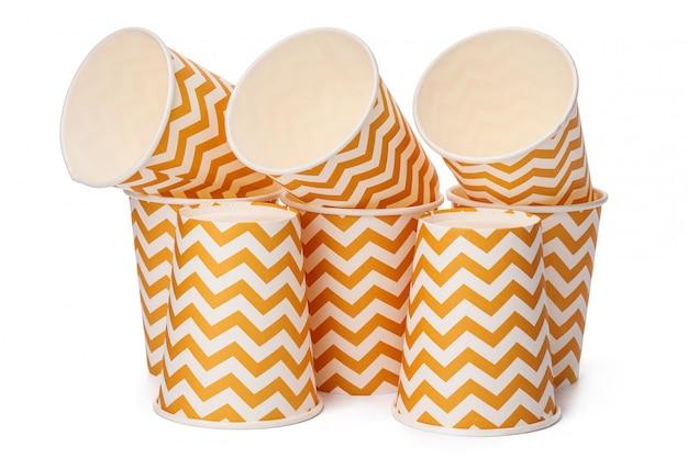 Куча картонных стаканчиков с бежевым геометрическим рисунком на белом фоне Premium Фотографии
