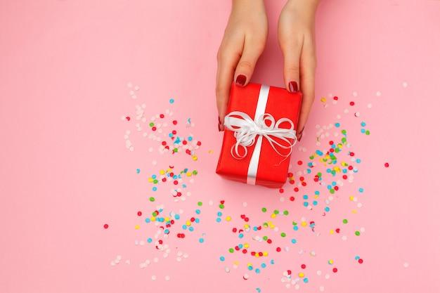 Женщина держит подарочную коробку на цветном фоне Premium Фотографии