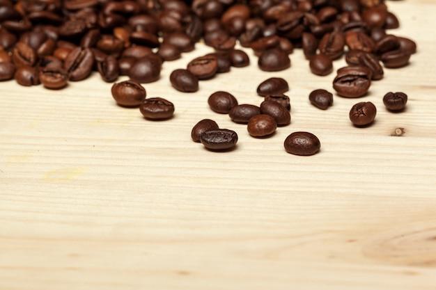 Крупным планом кофейных зерен на деревянном фоне Premium Фотографии