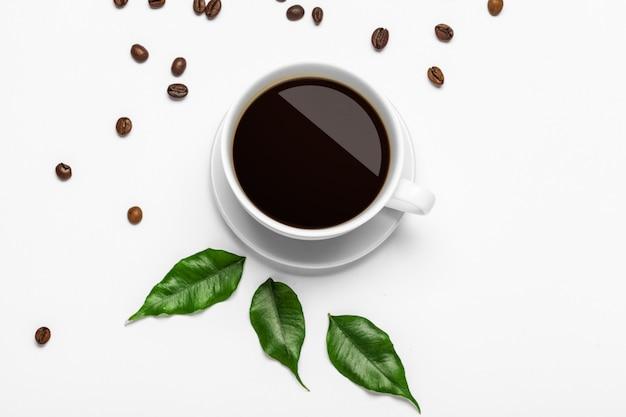 コーヒーカップと白い背景の上の豆 Premium写真