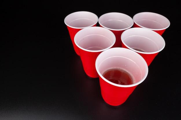 Красные пластиковые стаканчики и мячик для игры в пивной понг Premium Фотографии
