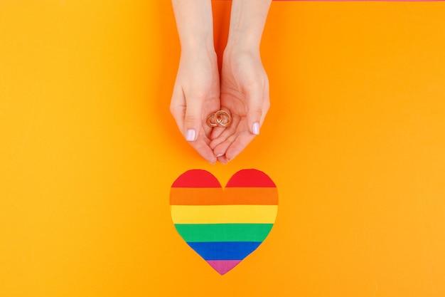 Концепция брака геев с радужным флагом и кольцами Premium Фотографии