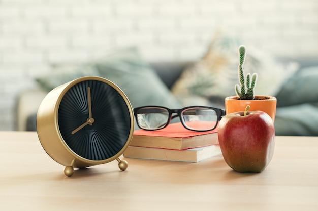 Пришло время для школы. старинный будильник и яблоко на деревянный стол Premium Фотографии