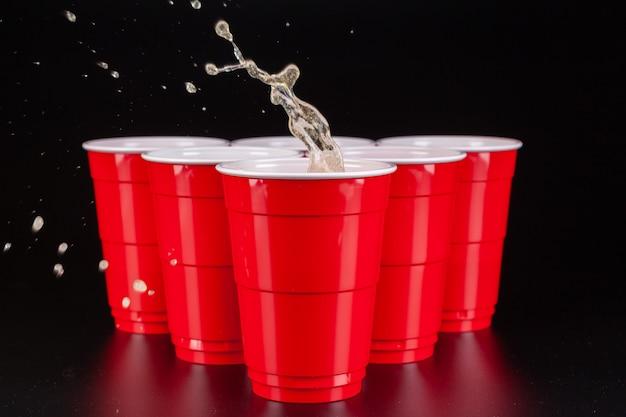 ビールピンポンのゲームのための赤いプラスチックカップの配置 Premium写真