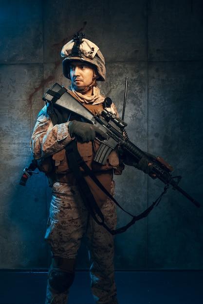 Молодой человек в военной форме наемного солдата в наше время Premium Фотографии
