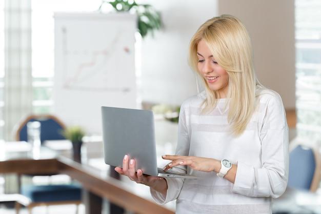 Улыбаясь зрелая женщина держит ноутбук Premium Фотографии