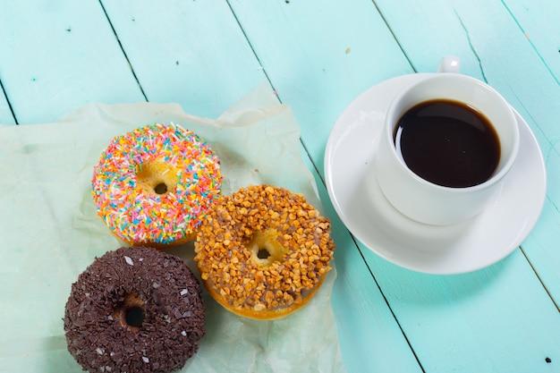 ドーナツと木製のテーブルの上のコーヒー。上面図 Premium写真