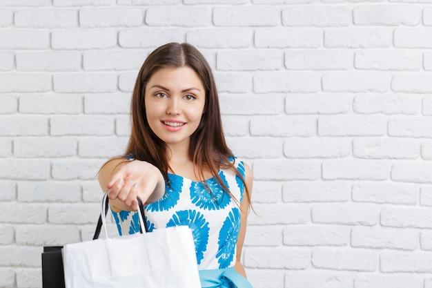 買い物袋を持つ若い幸せな笑顔の女性の肖像画 Premium写真