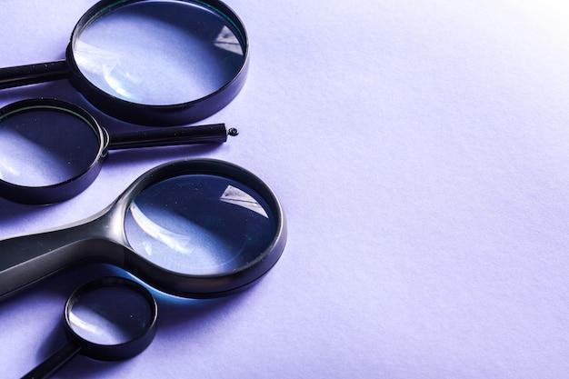 青色の背景に拡大鏡をクローズアップ Premium写真