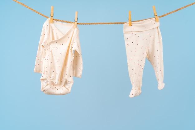 かわいい幼児のカラフルな服をロープに掛ける Premium写真