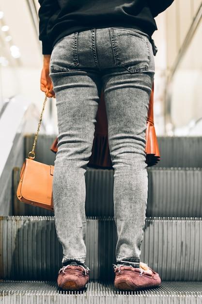 ショッピングモールのエスカレーターに立っている足 Premium写真