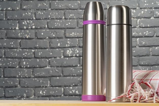 アルミ金属魔法瓶ボトルをテーブルの上にクローズアップ Premium写真
