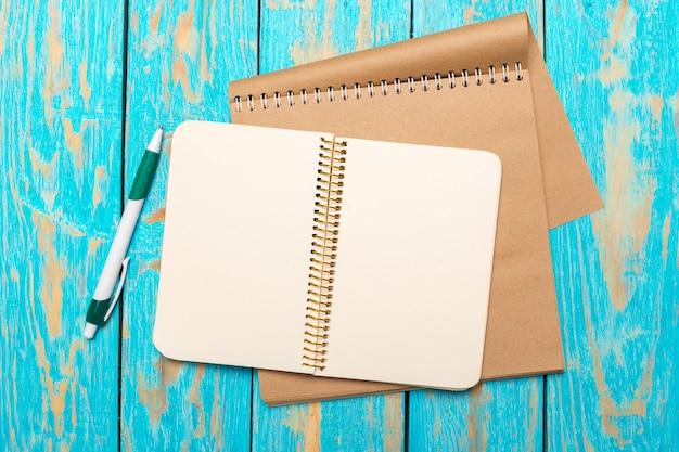 空白のノートブックと木製のテーブル背景にペンでトップビューワークスペース Premium写真