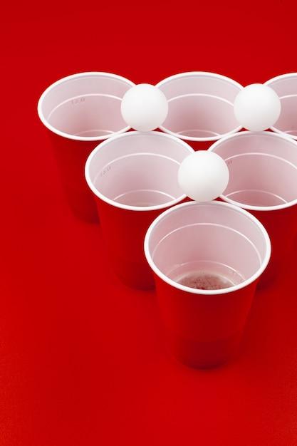 カップと赤の背景にプラスチックボール。ビールポンゲーム Premium写真