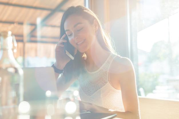 カフェテリアの女性は電話で話す Premium写真