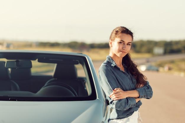Сексуальная женщина позирует рядом с кабриолетом Premium Фотографии