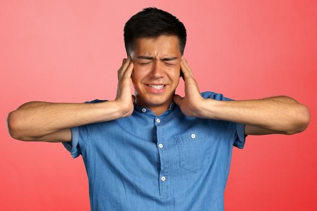 腹が立つ若い男が手で耳を差し込む Premium写真