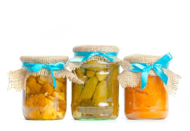 Консервированные овощи в стеклянных банках, изолированные на белом Premium Фотографии