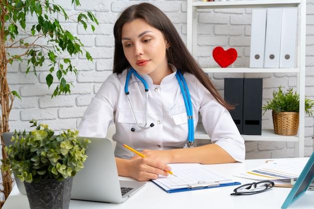 Молодой женский доктор кардиолог сидя на ее столе и работе Premium Фотографии