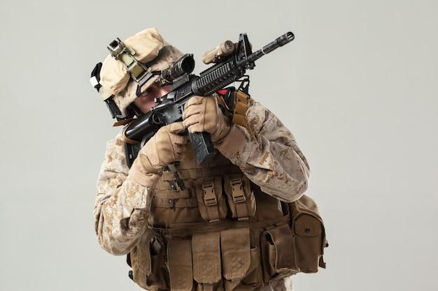 Солдат в камуфляже держит винтовку Premium Фотографии