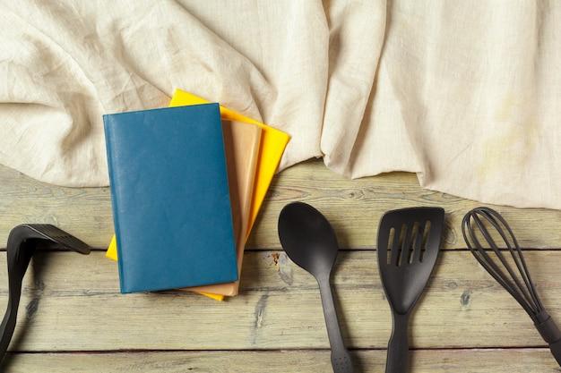テーブルクロス、コピースペースとテーブルの上の開いたメモ帳と台所用品の空白のシート Premium写真