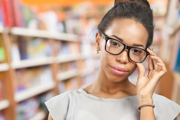 彼女の眼鏡を保持している若いアフリカ人女性 Premium写真
