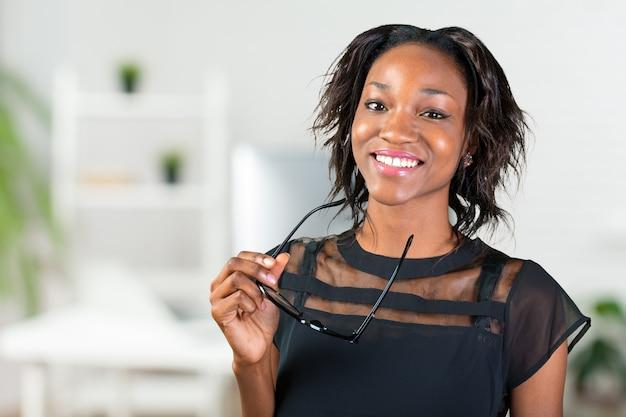 彼女の眼鏡を押しながら笑みを浮かべて若いアフリカ人女性 Premium写真