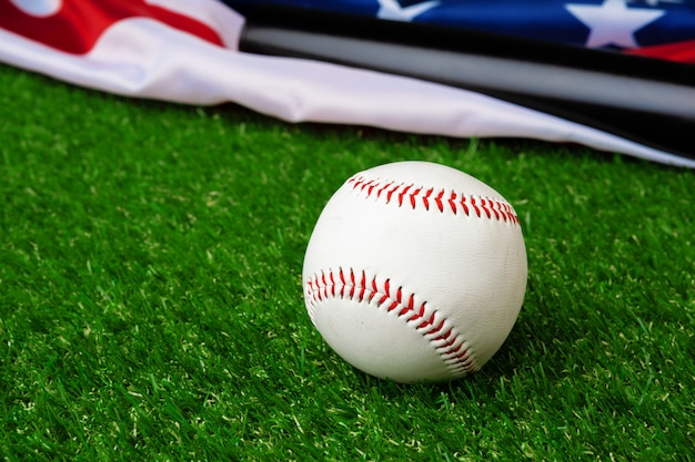 野球のバットと草の上のアメリカの国旗とボール Premium写真