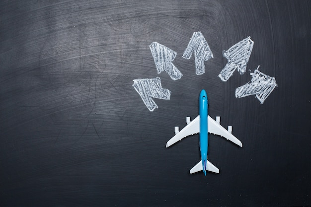 黒板背景と矢印図面上のおもちゃの飛行機 Premium写真