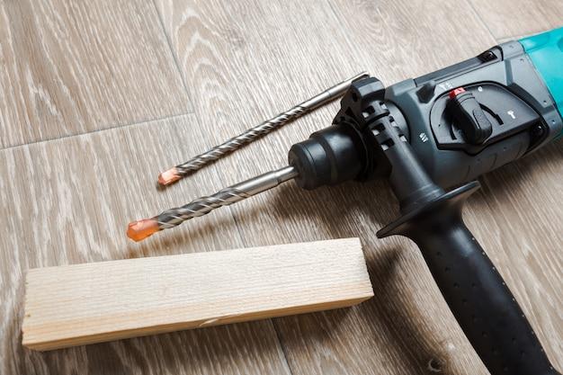 Электрическая перфоратор лежит на деревянном столе Premium Фотографии