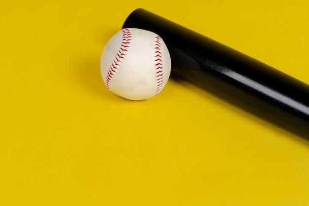 野球のバットと明るい黄色の背景にボール Premium写真