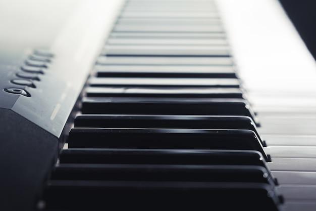 Клавиатура пианино крупным планом, вид сбоку Premium Фотографии