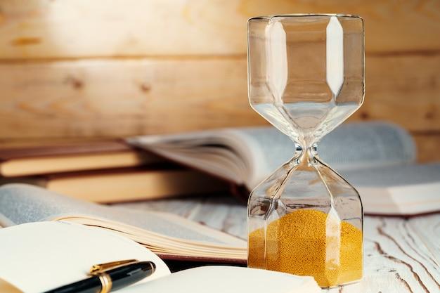 木製の表面に砂の砂時計をクローズアップ Premium写真