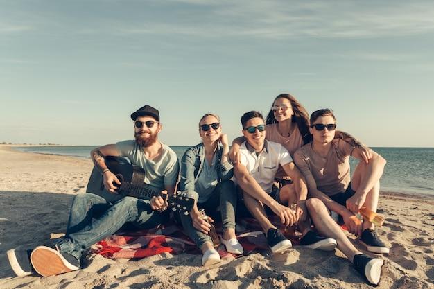 Группа друзей, веселятся на пляже Premium Фотографии