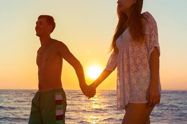 Пара гуляет на пляже Premium Фотографии