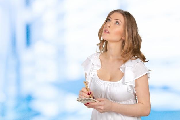 Молодая женщина с ручкой и блокнотом Premium Фотографии