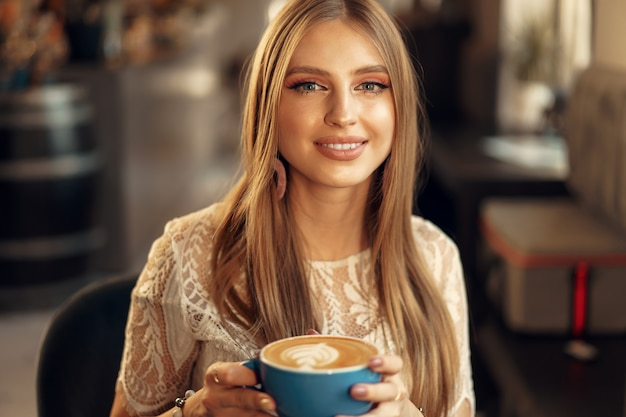 彼女の飲み物を楽しんでいるコーヒーショップに座っている美しい若い女性 Premium写真
