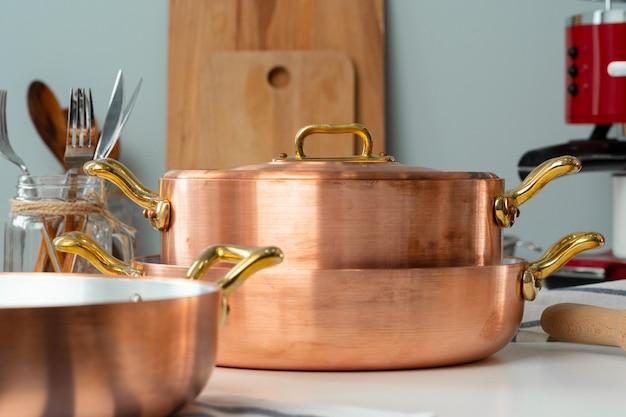 銅の調理器具とモダンなキッチンインテリアのクローズアップ Premium写真