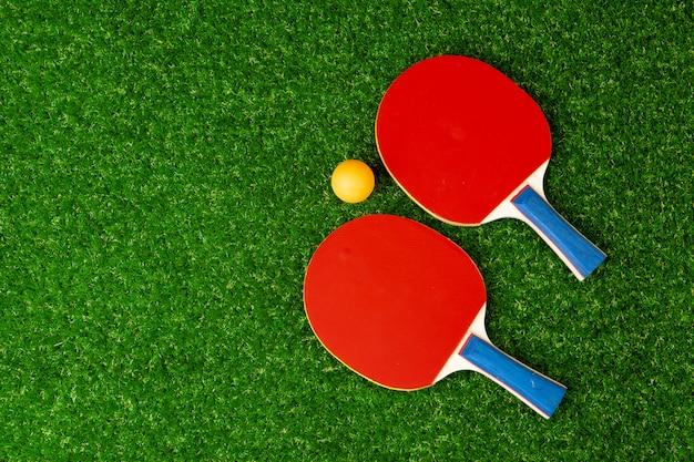 卓球ラケットと草の上のボール Premium写真