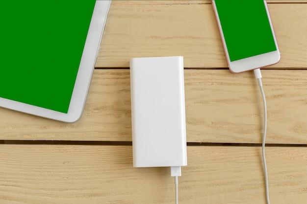 パワーバンクと木製のテーブルの上の携帯電話 Premium写真
