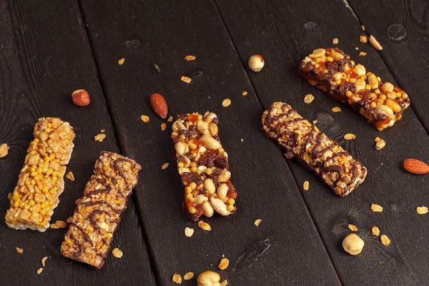 Здоровые батончики с орехами, семечками и сухофруктами на деревянном столе Premium Фотографии